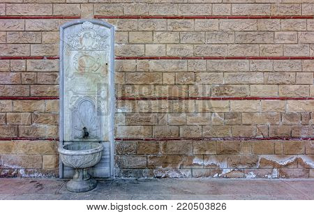 Old, ornate, embossed white marble fountain on a historical wall