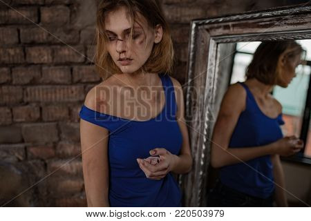 Beaten sad woman victim of domestic violence and abuse stands near mirror with bruises and wounds on her bloody face and body. Сoncept of domestic violence, sexual violence and cruelty.
