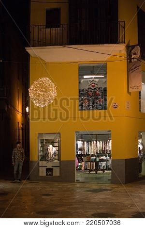 PALMA DE MALLORCA, BALEARIC ISLANDS, SPAIN - DECEMBER 5, 2017: Camisas de Victor shirt boutique with evening Christmas light decorations on December 5, 2017 in Palma de Mallorca, Balearic islands, Spain.