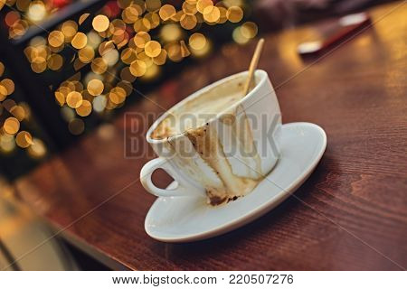 White cup with energetic aroma coffee on a table with illumination lights in the background.