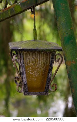 a vintage style street light with crown on the top. Beautiful historical retro metal Streetlight on green tree background.