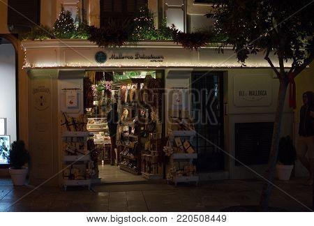 PALMA DE MALLORCA, BALEARIC ISLANDS, SPAIN - DECEMBER 5, 2017: Mallorca Delicatessen storefront in Old Town shopping street with evening Christmas light decorations on December 5, 2017 in Palma de Mallorca, Balearic islands, Spain.