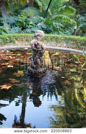 MALAGA, SPAIN - DECEMBER 19, 2017: Detail of sculpture in pond with reflections in green vegetation in Jardin de la Concepcion on December 19, 2017 in Malaga, Spain