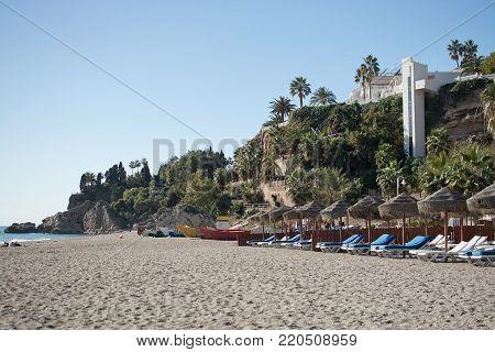 NERJA, MALAGA, SPAIN - DECEMBER 19, 2017: Sunlit but empty beach sun lounge chairs on Burriana beach on December 19, 2017 in Nerja, Malaga, Spain