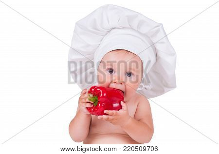 A funny little girl in a chef's clothes is eating pepper