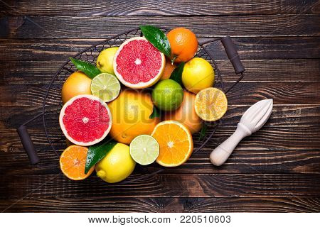 Citrus fruits and cooking citrus juice background. Assorted fresh citrus fruits with leaves. Orange, grapefruit, lemon, lime, tangerine on wooden table. Healthy eating, diet, vegetarian food concept. Top view