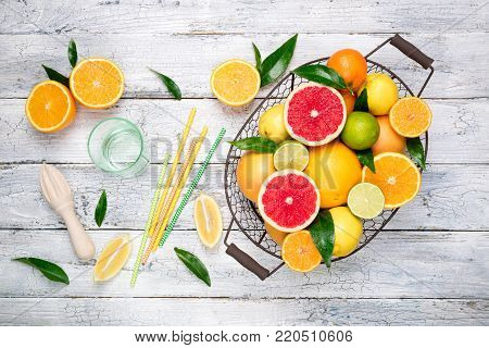 Citrus fruits background. Assorted fresh citrus fruits with leaves. Orange, grapefruit, lemon, lime, tangerine. Cooking citrus juice. Top view