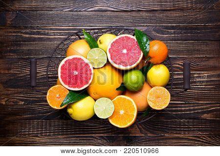 Citrus fruits background. Fruits in basket orange, grapefruit, lemon, lime, tangerine. Assorted fresh citrus fruits with leaves. Top view
