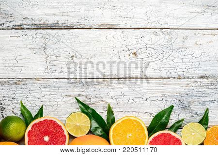 Citrus fruits background. Fruits in basket orange, grapefruit, lemon, lime, tangerine. Assorted fresh citrus fruits with leaves. Top view, flat lay. Copy space
