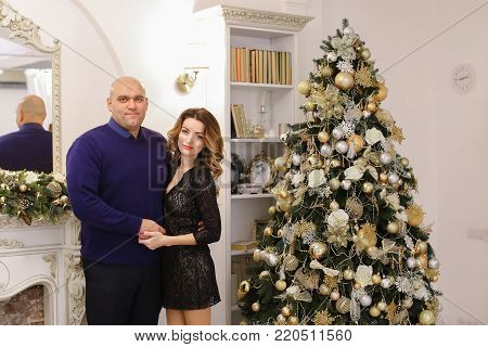 Beautiful spouses, loving husband and wife smile and look at camera, pose and hug each other in bright living room with fireplace decorated in festive. Woman of European appearance with long curly blond hair dressed in beautiful black dress