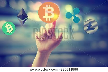 Cryptocurrency with hand pressing a button on blurred abstract background