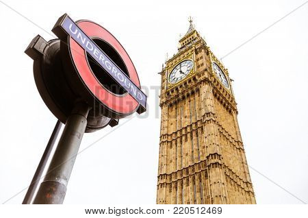 London, UK - 5th June 2017: The houses of Parliament clock tower, Big Ben, with a London Underground sign in the foreground, against white sky background.