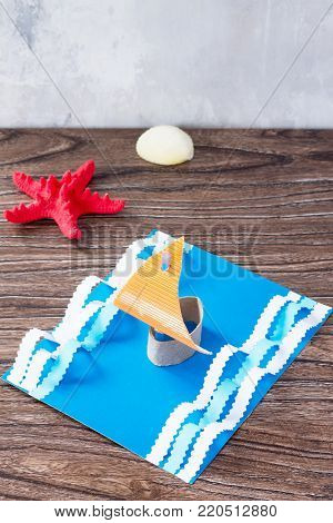 Craft Paper Boat, The Concept Of Father's Day Congratulation. Starfish And Seashells On A Wooden Tab