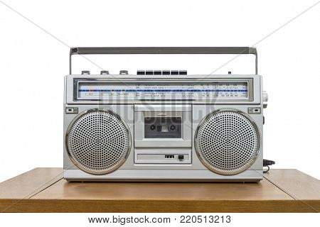 Vintage portable boom box tape player on old wood table isolated on white.