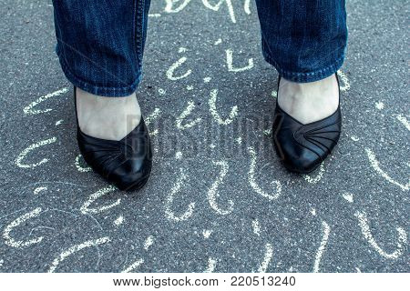 Woman in shoes standing on the asphalt road. On the road with chalk drawn many question marks.