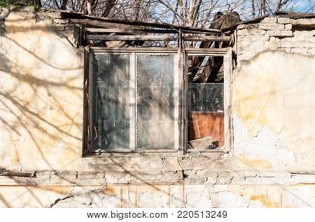 Remains of abandoned damaged and destroyed house by grenade shelling with collapsed roof in the war zone
