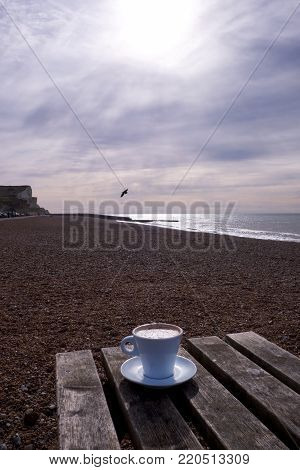 a white coffee cup and saucer full of cappuccino coffee with chocolate on top, on a wooden table on a pebble beach in the winter with the sea, sky and cliffs in the background, a seagull in the sky