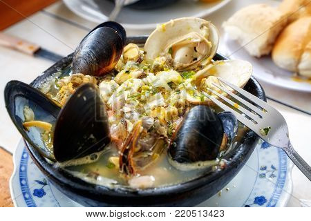 Paila marina served in Santiago de Chile. It is a traditional Chilean seafood soup with shellfish, fish and a variety of herbs and spices such as paprika and parsley.