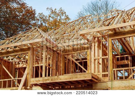 A stick built house under construction New build roof with wooden truss, post and beam framework.