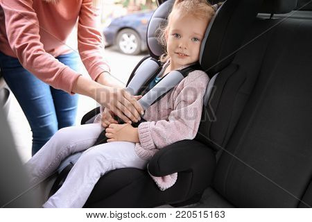 Young woman fastening security belt to girl in car