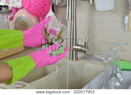 Washing a wine glass  wearing rubber pink gloves above a kitchen sink