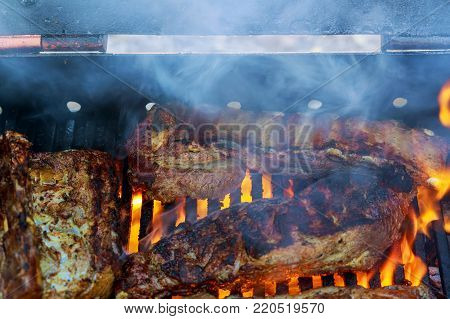 Spare ribs cooking on barbecue grill for Grilled pork ribs on the flaming grill