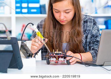 Schoolgirl in the school robotics laboratory with a robot model