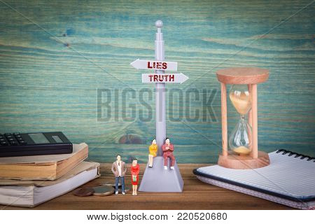 Lies and truth. Signpost on wooden table.