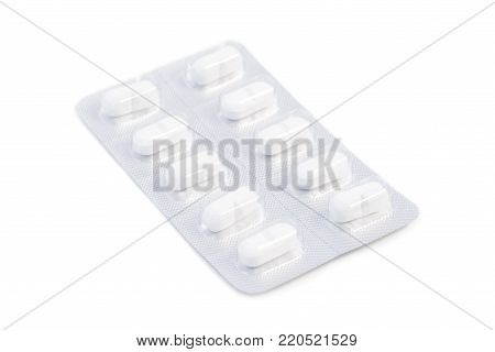 Close-up of white medicine pills in an unused blister pack, isolated on white background.