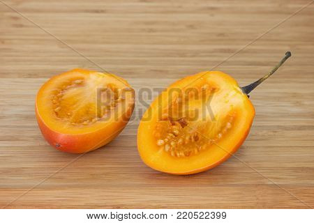 Close-up of a tamarillo (also known as tree tomato (Solanum betaceum)) cut in half on a wooden chopping board, isolated on white background.