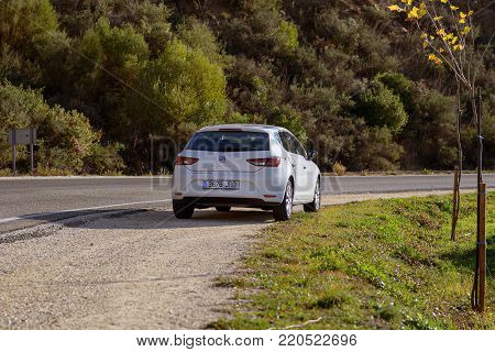 MALAGA, SPAIN - DECEMBER 2017:  White Seat Leon stays parked among clouds on road of Crete island. Seat Leon is a compact hatchback derived from the Seat.