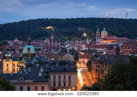 View of old buildings at the Mala Strana District (Lesser Town) and Petrin Hill in Prague, Czech Republic, at dusk.
