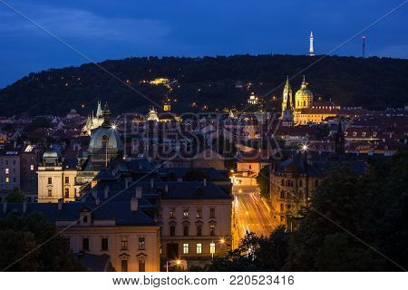 View of old buildings at the Mala Strana District (Lesser Town) and Petrin Hill in Prague, Czech Republic, at night.