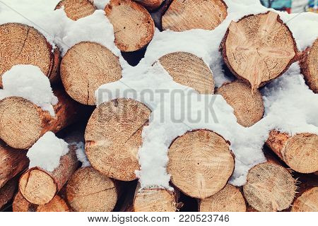 Pile of firewood background. Firewood stacked in a pile of snow on the street. Winter weather is snowing. Winter background.