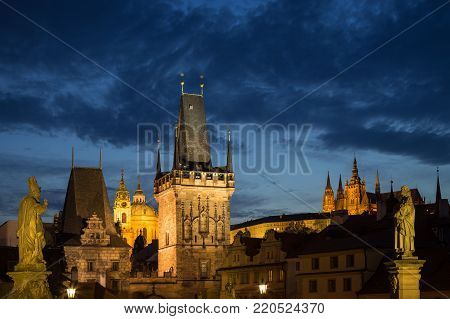 View of lit statues, Lesser Town Bridge Towers, St. Nicholas Church and Prague (Hradcany) Castle at the Mala Strana (Lesser Town) in Prague, Czech Republic, in the evening. Copy space.