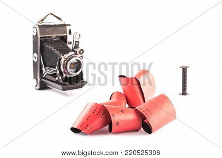 120 film for medium format retro cameras on white background with shadows, blurry vintage cameras with plastic spool on background, auctions, hobby and collections