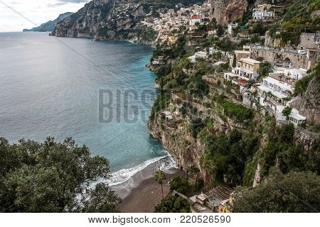 Sea shore vista with foaming waves on a beach and a small town on a rocky coastline