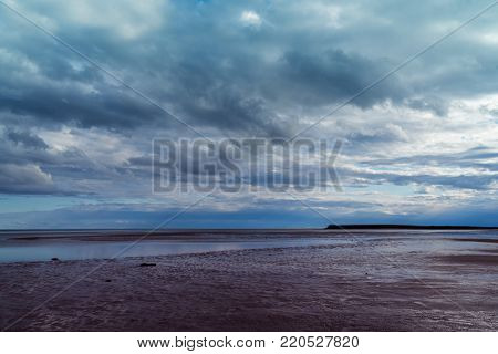 Stormy skies over the shore at low tide.