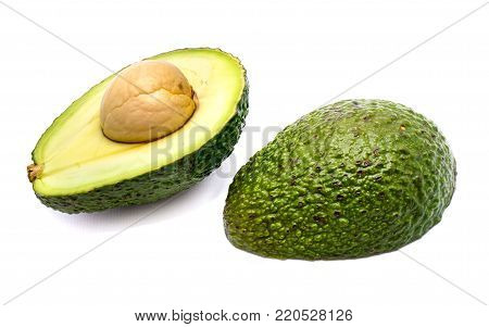 Avocado halves (Persea americana, alligator pear) with a stone isolated on white background