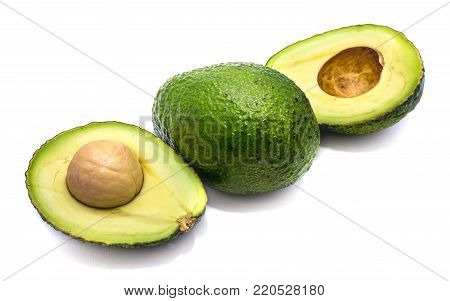 Whole and avocado halves (Persea americana, alligator pear) with a stone isolated on white background