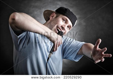 Rapper attitude rap singer hip Hop Dancer performing. Young man with microphone singing hand cool gesture black grunge background