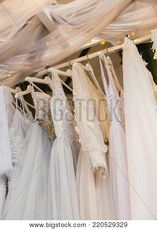 Few beautiful pastel wedding dresses on a hanger.