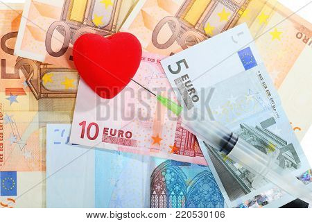medical treatment and high cost for health care service concept: red heart syringe on money euro paper banknotes