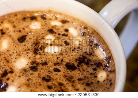 Close up top view of hot chocolate in white cup