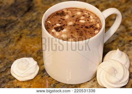 Hot chocolate in white mug with homemade french meringue marshmallows on brown marble