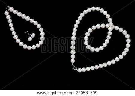 White pearls necklace, earrings and bracelet on black background