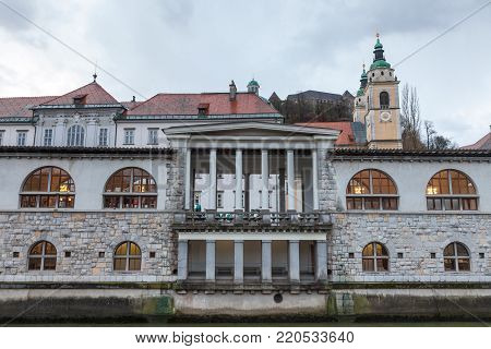 Central Market of Ljubljana, capital city of Slovenia, taken during a cloudy rainy day, with the Ljubljanica river on foreground. This part of the old town of Ljubljana is considered to be one of the symbols of the city