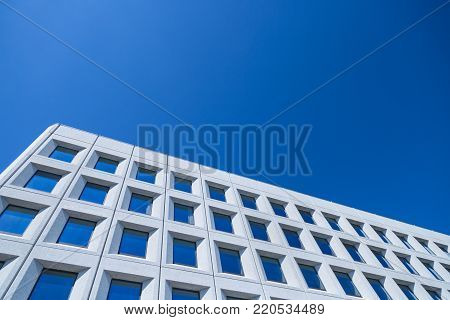 Abstract image of a modern architecture background, white building made of concrete and glass on a blue sky background