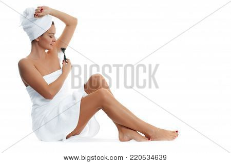 Young woman shaving armpit isolated on white background. Armpit epilation hair removal and skin care concept.