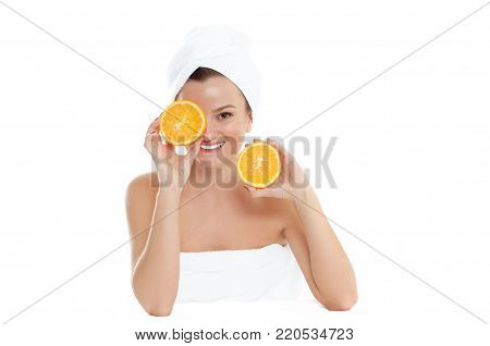 Beautiful young woman with clean fresh skin is holding two half oranges. Facial treatment, beauty and spa .